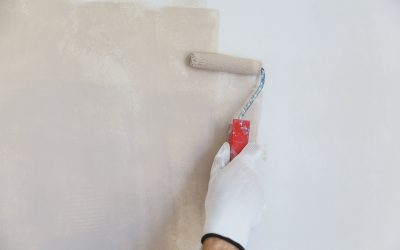 painter hand in white glove painting a wall with paint roller
